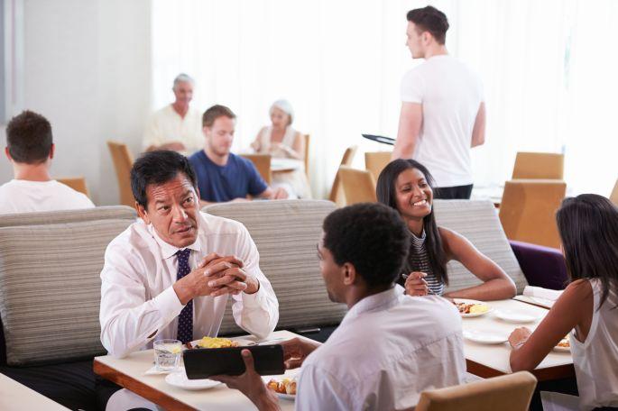 Businessmen Meeting Over Breakfast In Hotel Restaurant