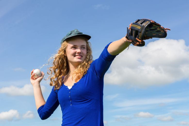 Young woman playing baseball with cap glove and ball